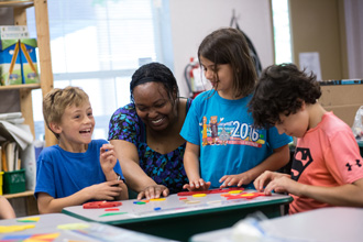 A teacher works with three students in a classroom.